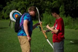 camper instructing another camper about shooting a bow and arrow
